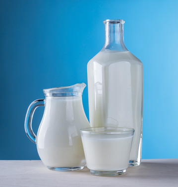 White milk in various glass bottles without induction seals